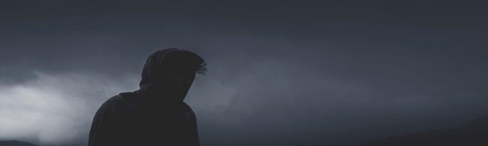 person looking into dark, stormy sky